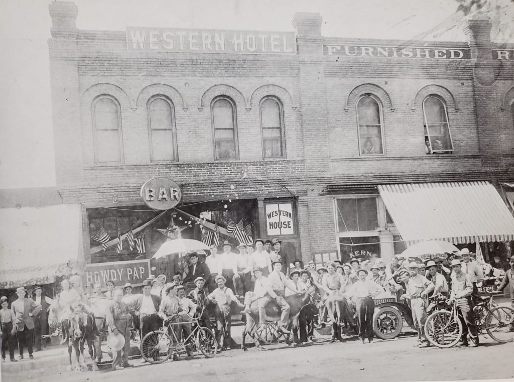 July 4, circa 1915. The Western Hotel is upstairs with the Leader Saloon downstairs at right and Crowell's Furniture Store on the left. This is on the south side of Sumner across from the SP Depot.
