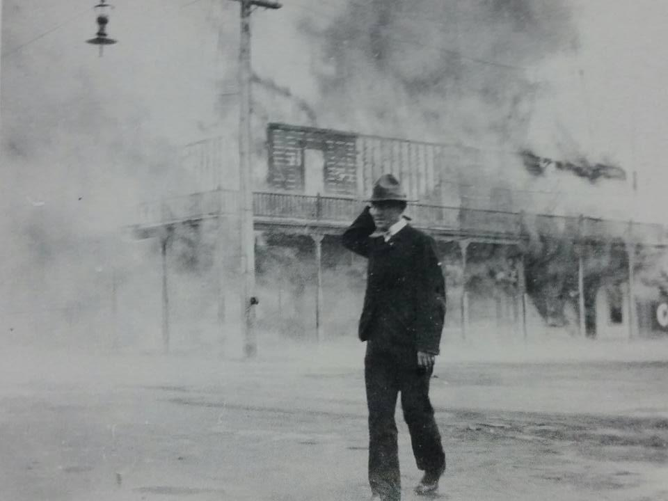 The Metropole Hotel burns in the background as a man passes by