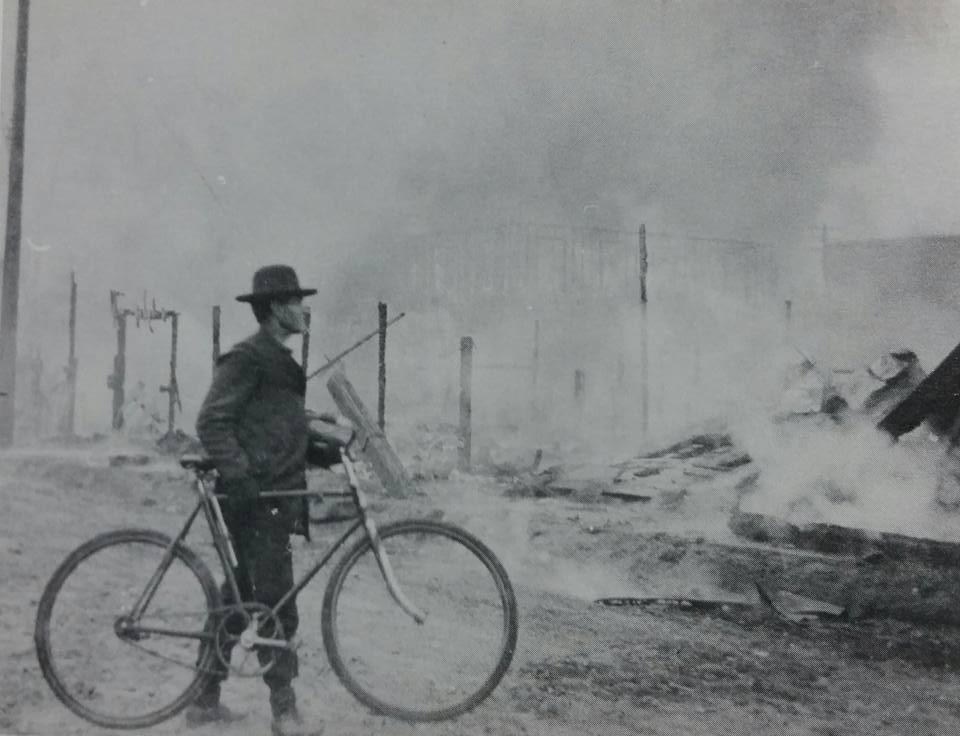 Fire at Humboldt (E. 21st) Street with man & bicycle